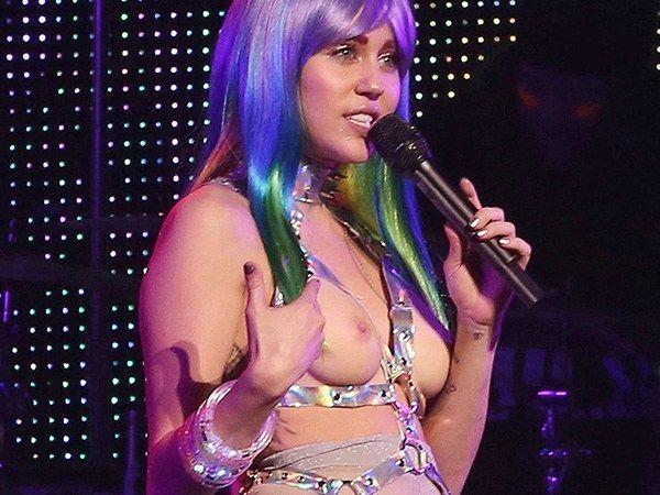 Miley Cyrus com roupa transparente em show mostrando a buceta e os seios