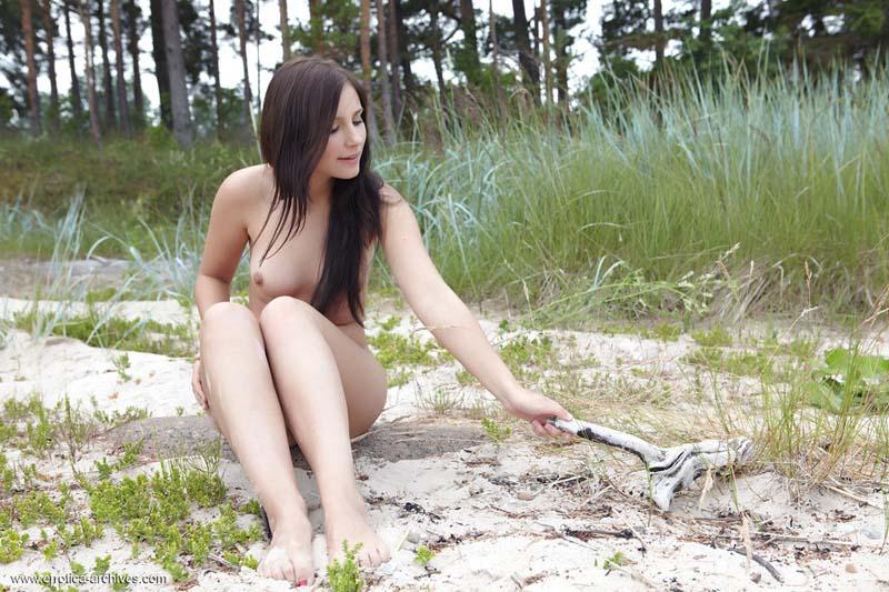 Morena linda sentada na areia pelada