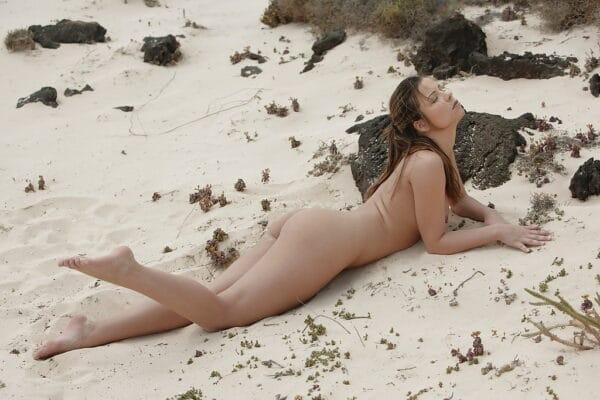 Moreninha nua na praia mostrando a buceta com bigodinho