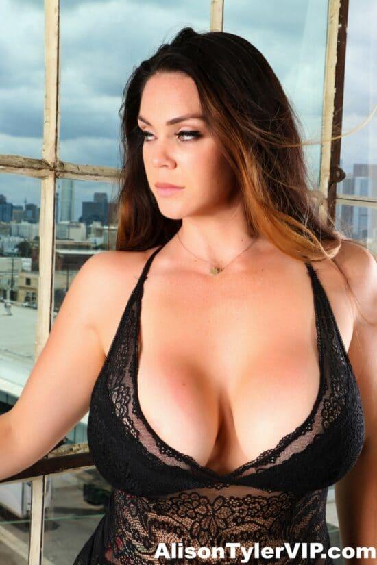 Ninfeta de lingerie preta mostrando os peitões